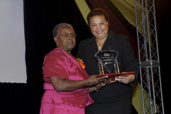 Edward Williams.  Caption: Dawn Smith (left) collects Regional Unsung Hero Awardee 2012 Edward Williams' award on his behalf from Managing Director, HR, CIBC FirstCaribbean, Ella Hoyos.