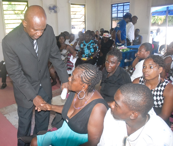 Minister Maxwell Charles extending condolences to the mother of Junior Mckie