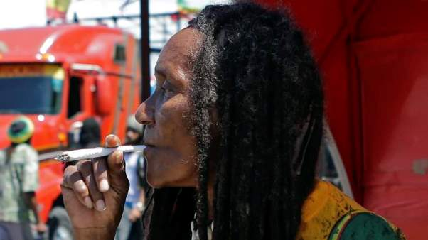 A man smokes marijuana during a pro-legalisation demonstration in Kingston. Photo courtesy http://news.sky.com/