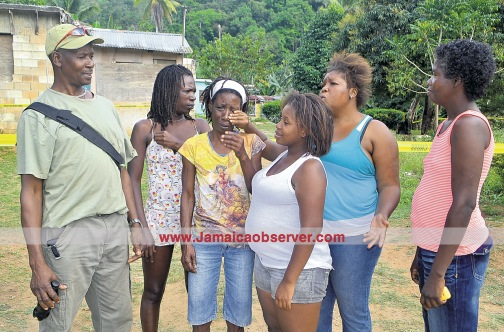 Family members discuss the killing yesterday. Photo by Phillip Lemonte, courtesy http://www.jamaicaobserver.com