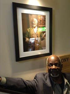 Joseph Marcell posing beneath a framed portrait of himself as King Lear at the Globe Theatre