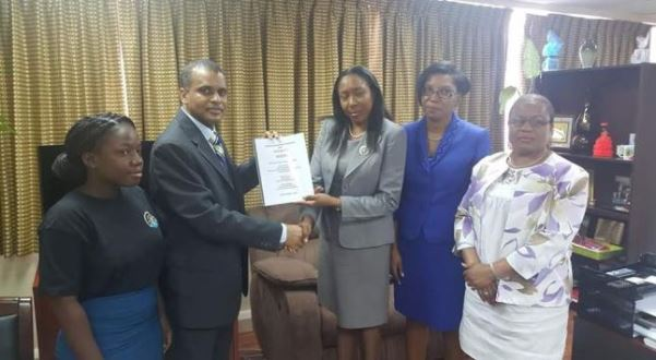 Williams presenting the petition to Minister Alvina Reynolds. Photo courtesy http://www.stlucianewsonline.com