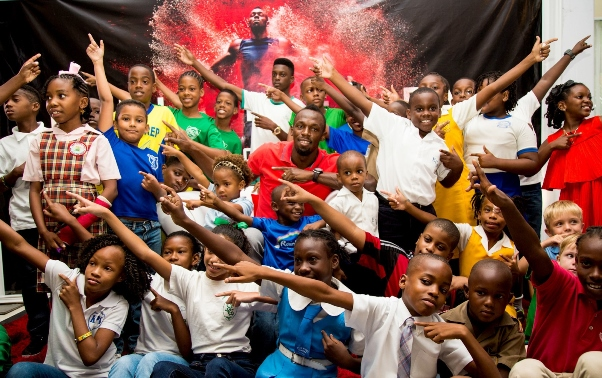"""Digicel invited aspiring little newshounds from across the Caribbean to a kiddie press conference with Usain Bolt, the world's fastest man in the hot seat. The kiddie press pack surrounds Usain for an impromptu lightning bolt having peppered him with probing questions like """"How many girlfriends do you have?"""" and """"What do you think of vegetables?"""" in Kingston, Jamaica on Tuesday. Photo courtesy http://www.prnewswire.com"""