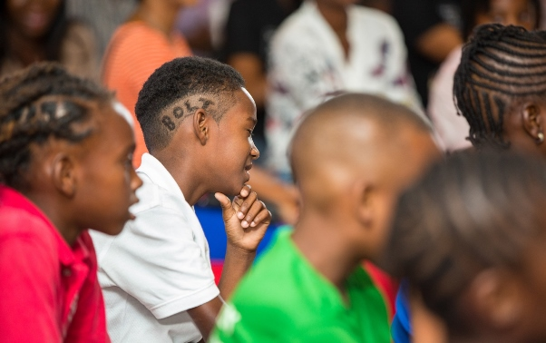 """Die hard Bolt fan, nine year-old Kareem Davis from St. Vincent and the Grenadines, is all ears as Usain fields questions from the kiddie press pack at the Digicel """"Bring the Beat"""" launch. Photo courtesy http://www.prnewswire.com"""