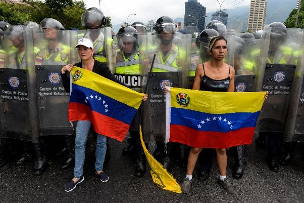 Anti-Maduro demonstrators hold national flags during a protest in front of members of the National Police in Caracas on May 11, 2016. Photo courtesy (AFP Photo/Juan Barreto and www.vidostream.com