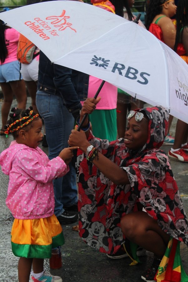 Mother adjusts daughter's raincoat at Kiddies carnival on Sunday. Photo courtesy CaribDirect