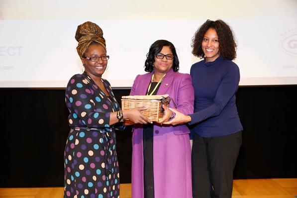 Mrs Carol Vaughan-Roberts, administrative director for CaribDirect and Mrs Nyree Chambers of Grace Foods UK presenting Ms Beverley Awonaya her gift basket. Photo courtesy CaribDirect