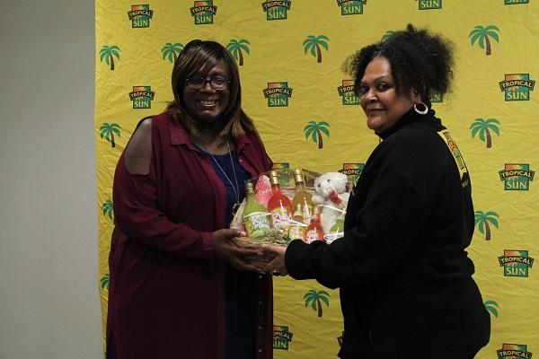 Dawn Lindo-Morgan receiving her Jewel Isle Rum Punch hamper from Tropical Sun's Vaseva Qarau. Photo courtesy CaribDirect