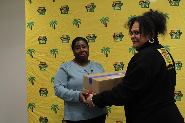 Margaret St John receiving her two boxes of Port Royal patties from Tropical Sun's Vaseva Qarau. Photo courtesy CaribDirect